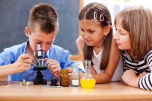 Két kislány és egy kisfiú mikroszkóppal vizsgál valamit
