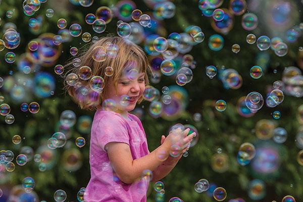 egy rózsaszín ruhás kislány buborékokkal játszik
