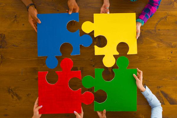 kezek színes puzzle darabokat illesztenek össze